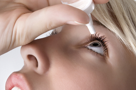 woman applying eyedroppes, close up