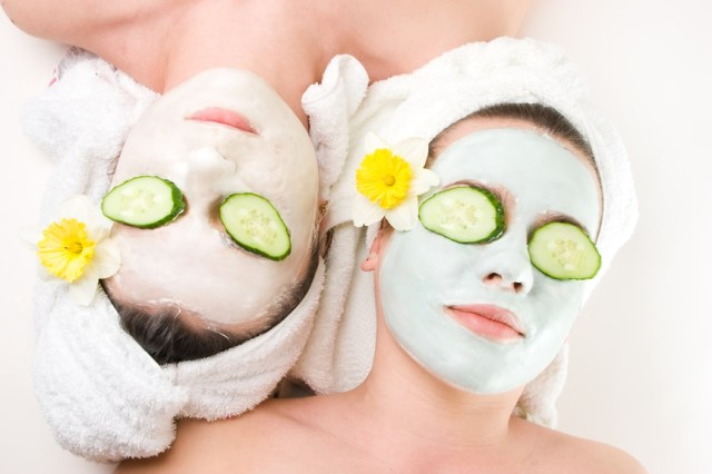 Two young female with skincare mask and cucumber on eyes