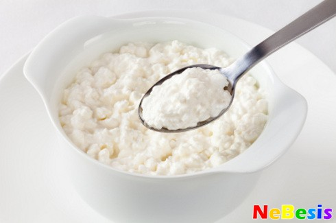 A bowl of cottage cheese, and a spoon lifting out a spoonful.