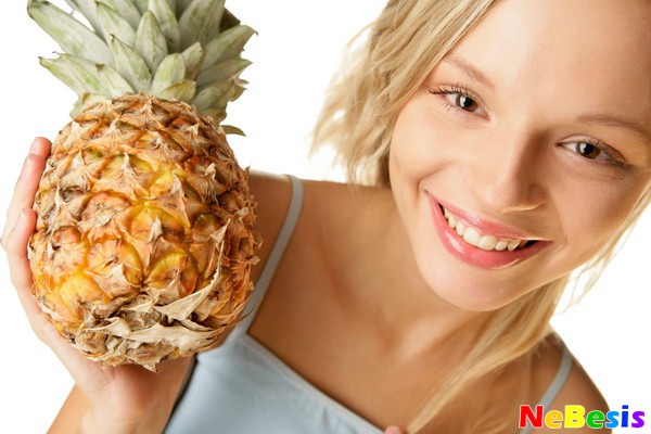 Portrait of young woman holding pineapple